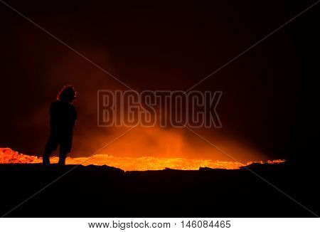 Person standing at the edge of Erta Ale active volcano in Afar Region in Ethiopia Africa at night.