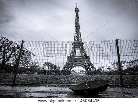 Eiffel tower and umbrella on a rainy day - Eiffel tower from Paris France and a black umbrella in black and white settings on a rainy day.