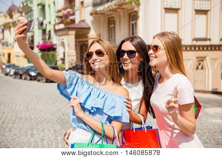 Three Happy Pretty Shoppers Making Photo On Smartphone