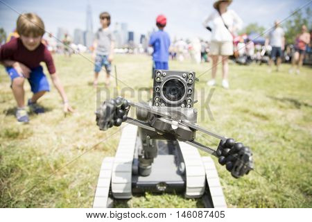 JERSEY CITY NJ MAY 29 2016: People watch a small unmanned ground vehicle the US Navy uses to locate and dispose of explosive devices during a demonstration at Liberty State Park for Fleet Week 2016.