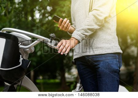 Man in sweater and jeans standing next to bike and holding phone. Image with lens flare effect