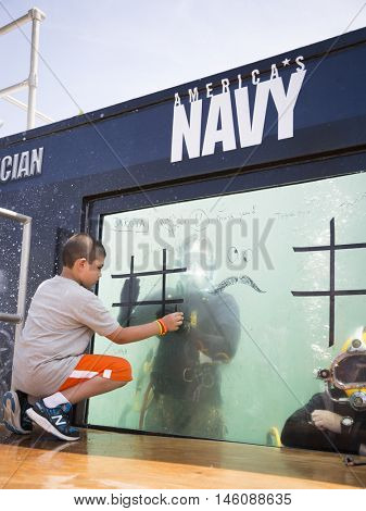 JERSEY CITY NJ MAY 29 2016: An unidentified boy plays tic tac toe with a US Navy EOD technician on the glass of a 6,800 gallon mobile dive tank during Fleet Week NY 2016 in Liberty State Park.