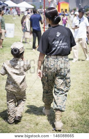 JERSEY CITY NJ MAY 29 2016: A female US Marine with a little girl wearing matching combat utility uniform walk in Liberty State Park in Jersey City, NJ during Fleet Week 2016.