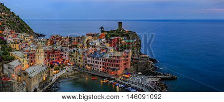 View from above hill of Vernazza bay and houses with lit light and blue sea at dusk one of Cinque Terre villages , Liguria, Italy