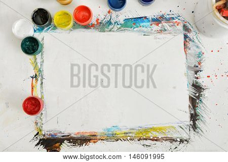 Top view of an artist's workplace with a sheet of paper and jars of different paint. Abstract art. Creativity and design. Drawing lesson. Art equipment.