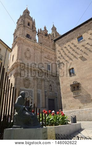 SALAMANCA, SPAIN - AUGUST 3, 2016: Monument to the Master Francisco Salinas next to the house of the shells and the Clerecia Church in Salamanca Spain
