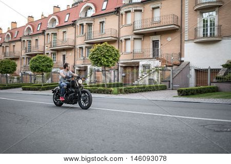 Stylish man rides on the black motorcycle on the urban background. He wears blue ripped jeans, a gray T-shirt with print, red sneakers, black moto gloves and sunglasses. He has a beard. Outdoors. Horizontal.