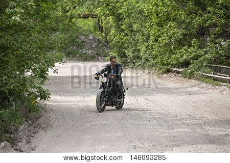 Handsome man with a beard rides on the dirt road on the black motorcycle on the nature background. He looks to the left. He wears black jeans, a dark-gray T-shirt with a print, black shoes, black gloves, a black leather jacket and sunglasses.