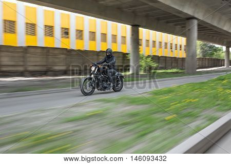 Guy in black helmet hurtling on the black motorbike on the road under the overpass. He wears a black leather jacket, black jeans, black shoes, black gloves and sunglasses. Outdoors. Horizontal.