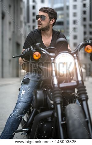 Bearded man sits on the black motorbike on the skyscraper background. Headlamp switched on. He wears a blue ripped jeans, a black T-shirt, black gloves and sunglasses. He looks to the right with parted lips.