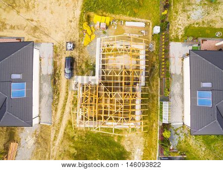 Construction site of new family house. Aerial view of area for pleasant living in suburban district. Construction industry from above.