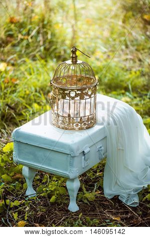 The decor for the wedding photo shoot. The white suitcase on legs, metal cage and a piece of white chiffon
