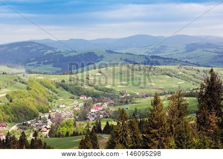 landscape consisting of a Carpathians mountains with green grassy valley fir-trees and houses on the foreground and cloudy skies on the background