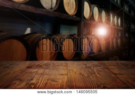 Wooden table in a wine cellar with barrels and sunlight