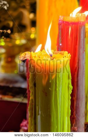 Burning red and yellow beautiful old textured candles with defocussed background of buddhist temple Thailand. Mood of sacrament and revelation.