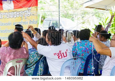 CHIANG RAI THAILAND - SEPTEMBER 1 : unidentified people taking holy thread on their head in Thai traditional rites on September 1 2016 in Chiang rai Thailand.