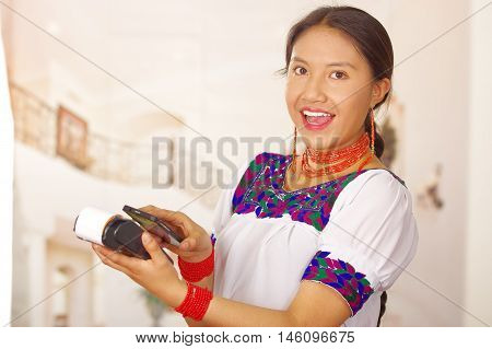 Young brunette wearing traditional native clothes working as hotel receptionist with friendly smile, processing payment using credit card terminal and mobile phone, customers point of view.