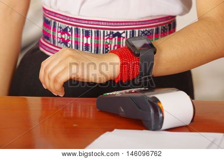Closeup female receptionist wearing traditional andean clothing, processing payment using credit card terminal and wrist watch, customers point of view.