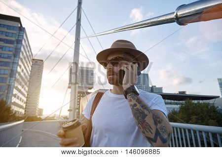 Tourist Talking On The Phone And Holding A Coffee