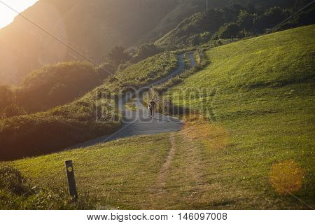 Surfer Walking Up A Hill On  Winding Road