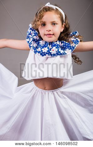 Cute little girl wearing beautiful white and blue dress with matching head band, actively posing for camera, studio background.