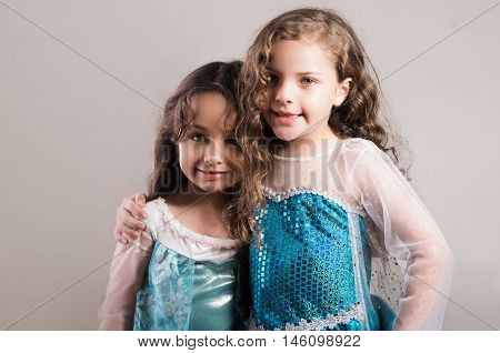Adorable big and little sister wearing matcing blue dresses posing together happily, studio background.