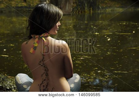 Sexy brunette topless woman as seen from behind, sitting down next to water lake, beautiful tattoo alongside entire spine, face partly visible.