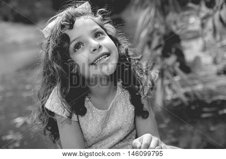 Cute little girl wearing beautiful blue dress with matching head band, posing for camera, outdoors lake background, black and white edition.