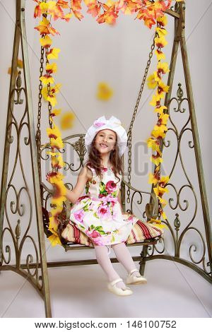 Gentle little girl in a white dress with roses and a white hat. Girl swinging on an old swing.