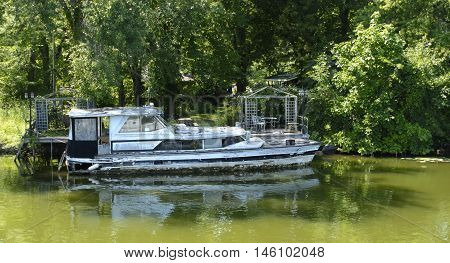 An abandoned pleasure craft run aground and decaying.