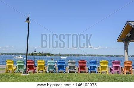 An inviting row of Adirondack Chairs lining the waterfront of Clayton NY USA in the 1000 Islands region.