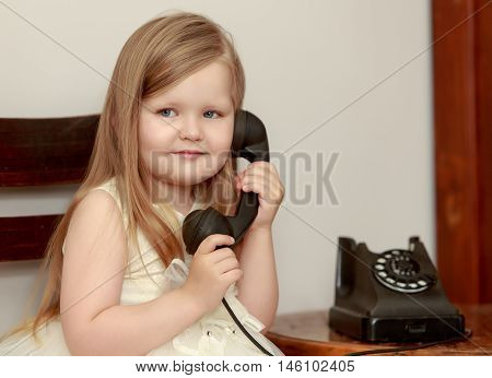 Cute little chubby girl with long, blonde hair below the shoulders, holds up the old phone