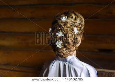 Portrait of attractive young woman with beautiful hairstyle and stylish hair accessory from polymer clay, rear view