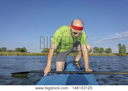 muscular, senior male paddler on a stand up paddleboard on a lake in Colorado