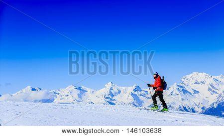 Ski touring in high mountains in fresh powder snow in sunny day. Snow mountain range. Mt Fort Peak Alps region Switzerland.Wallis