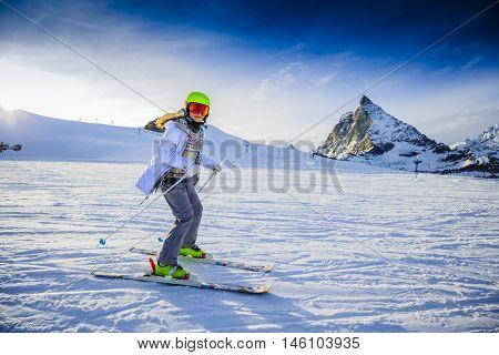 Teenager girl skiing on ski slope with Matterhorn in background in sunny day. Zermatt, Switzerland, Wallis region.
