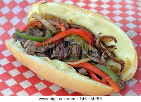 Philly Cheese Steak Sandwich: Served on a red check piece of paper. Close-up of rib grilled eye steak strips, bell peppers and onion in a hoagie style bun lined with provalone cheese slices.