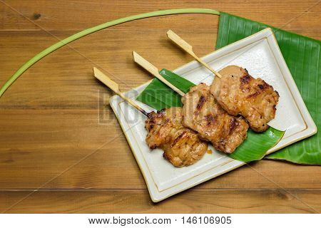Thai styled pork barbeque (Grilled pork) on a plate with green banana leaf on wooden table