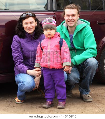 Family, mother, father and child, in outwear hunker down in front of car and smile