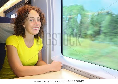 Woman rides in  speed train near window