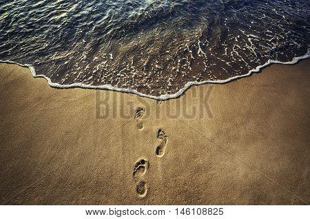 Footsteps on the sandy beach sunrise shot.