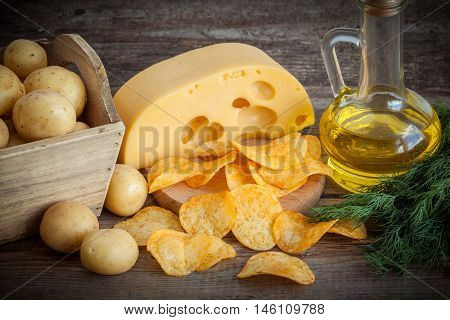 Crispy Potato Chips With Cheese, Potatoes In Wooden Box And Oil For Frying On Kitchen Table.