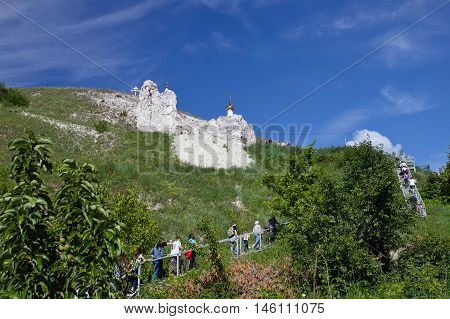 DIVNOGORIE VORONEZH REGION RUSSIA - JUNE 12 2016: People walk upstairs to the cave church Orthodox cathedral carved out of natural rock Russia Voronezh region museum Divnogorie in June 12 2016