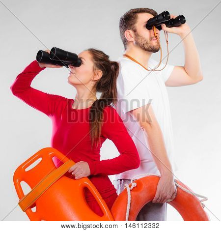 Accident prevention and water rescue. Young man and woman lifeguards on duty looking through binoculars keeping buoy lifesaver equipment on gray