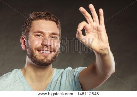 Portrait of happy smiling handsome man guy giving ok okay sign gesture in studio on black.
