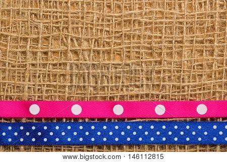 Polka dot pink and navy blue ribbon on brown mesh material natural burlap background