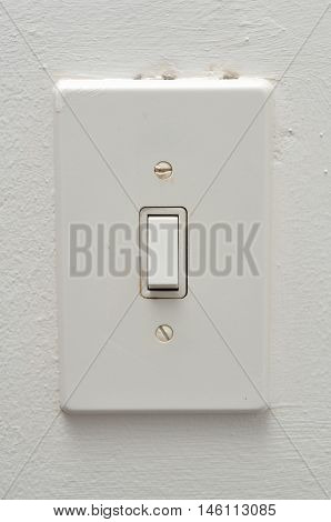 A white electrical light switch on a wall