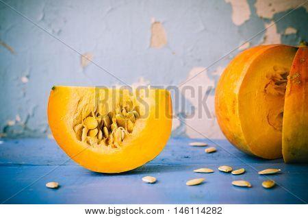 Autumn pumpkin with pumpkin seeds on blue wooden background. Thanksgiving Halloween Autumn holidays background concept. Selective focus.