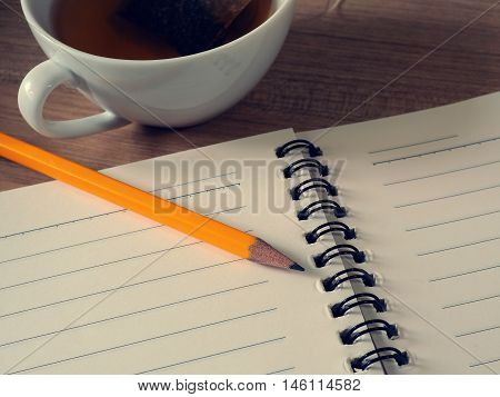 Office table with notebook, pencil and cup of tea. Minimal style concept for simply working.