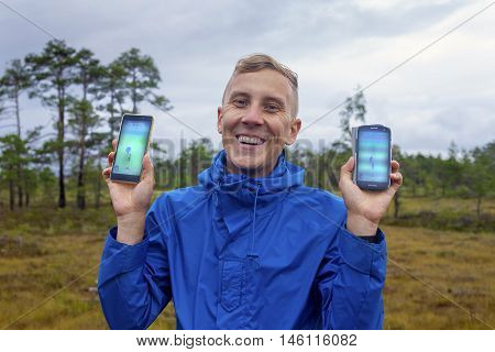 Voiste Estonia - August 13 2016: Happy young man playing Pokemon Go at countryside in rainy weather